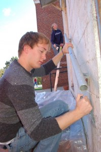 Andrew Fisher, a 4th year student at UVA and Julia Cooper, a 3rd year student, scrape paint from the back of the RVCC.
