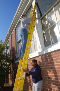 Briana Evans, a second year student at UVA, holds the ladder for Erin as she removes old storm windows from the building.