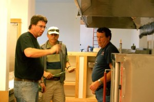 Left, Shawn Goodwin, Executive Chef at Devil's Backbone, discusses new kitchen equipment with Crandall, center, and one of the equipment suppliers.