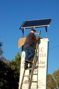 Jim Purvis, Local Electrician, Removes The Covering From The Solar Panel Above The Basic Necessities Sign In Nellysford, Virginia
