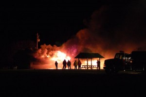 Photo By Tommy Stafford : Fire crews stand by as an old portable classroom at RVCC is intentionally burned.