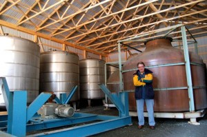 Chris stands in front of an additional load of distilling equipment that recently arrived.