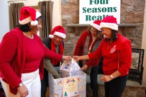 Members of the Four Seasons office pack the toy boxes at their office.