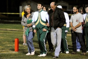 Leslie Tal, left, and husband Rafael Tal, (Of Mark Addy Inn -  Nellysford)  right, walk onto the field with son, Jacob at Friday night's game.