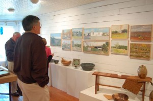 Customers stop to look over a recent local art display at Spruce Creek.
