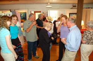 Russ Reid, far right, chats it up with customers at a past art show in Spruce Creek Gallery.