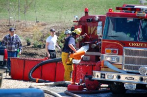 Crews from Crozet and Wintergreen work to dump water into a temporary basin to fight the fire.