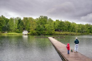 A father and son fish from the pier at Lake Monacan under threatening skies.