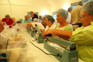 Area church volunteers seal bags of rice and other grains at Grace on Wednesday afternoon.