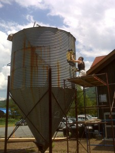 Photo By Tommy Stafford : ©2009 www.NelsonCountyLife.com : Merideth Young-Fogleman, owner of Black Rock Gallery at Wintergreen enjoys a sunny day while painting a logo on this silo at Devils Backbone Brewery in Roseland/Beech Grove.