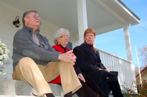 Hamner, Grinnell, and Walmsley sit on the front porch of the house in Schuyler where Earl grew up as a young man. The house was just renovated and opened for a tour Saturday.