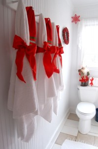 Simple but elegant. Red ribbon and bows decorate bath towels in the cottage.