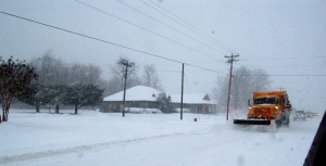 A VDOT snow plow pushes snow off of Route 151 in Nellysford, Virginia.