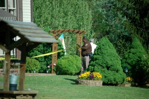 ©2010 www.nelsoncountylife.com : A Nelson County Sheriff's Deputy unrolls crime scene tape at a residence on Dark Hollow Lane in the south part of Nelson County near Roseland.