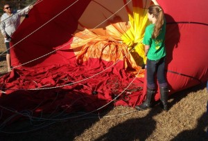 North Branch students Trena Garland and Lily Gates hold onto the hot air balloon as it starts to inflate on the ground.