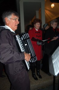 In addition to Santa's arrival at Stoney Creek, it was also their annual tree lighting ceremony and Christmas caroling. (L) Dr. Tom Krop of Afton plays accordion tunes for the season.