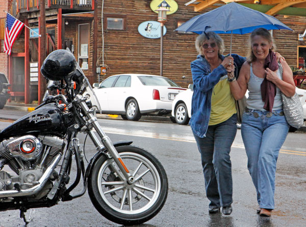 Floyd Friday night celebrants scramble to avoid a thunder shower Friday afternoon on Locust Street in Floyd.