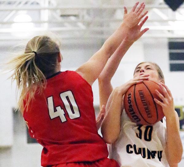 Varsity Lady Buff Madison Harris in action below the basket.