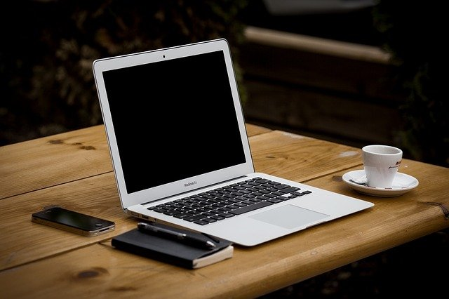 An IT professional's workstation - laptop, notebook, coffee.