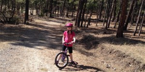 Girl straddling mountain bike on dirt path in forest