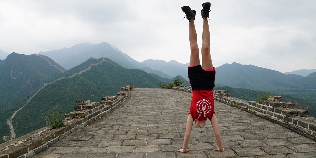 Sophie practising her hand stands on the Great Wall