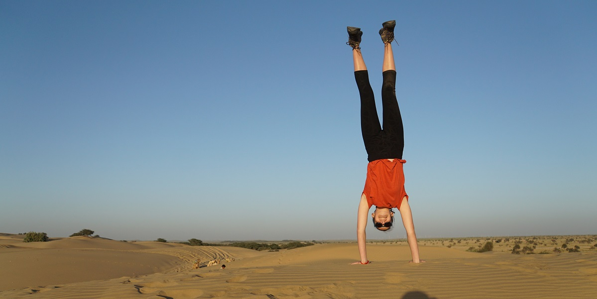 Sophie does a handstand on the top of a sand dune