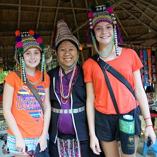 The girls try on traditional headdresses of the Akha hill tribe