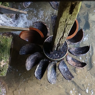 Water runs onto paddle wheels that turn a grindstone