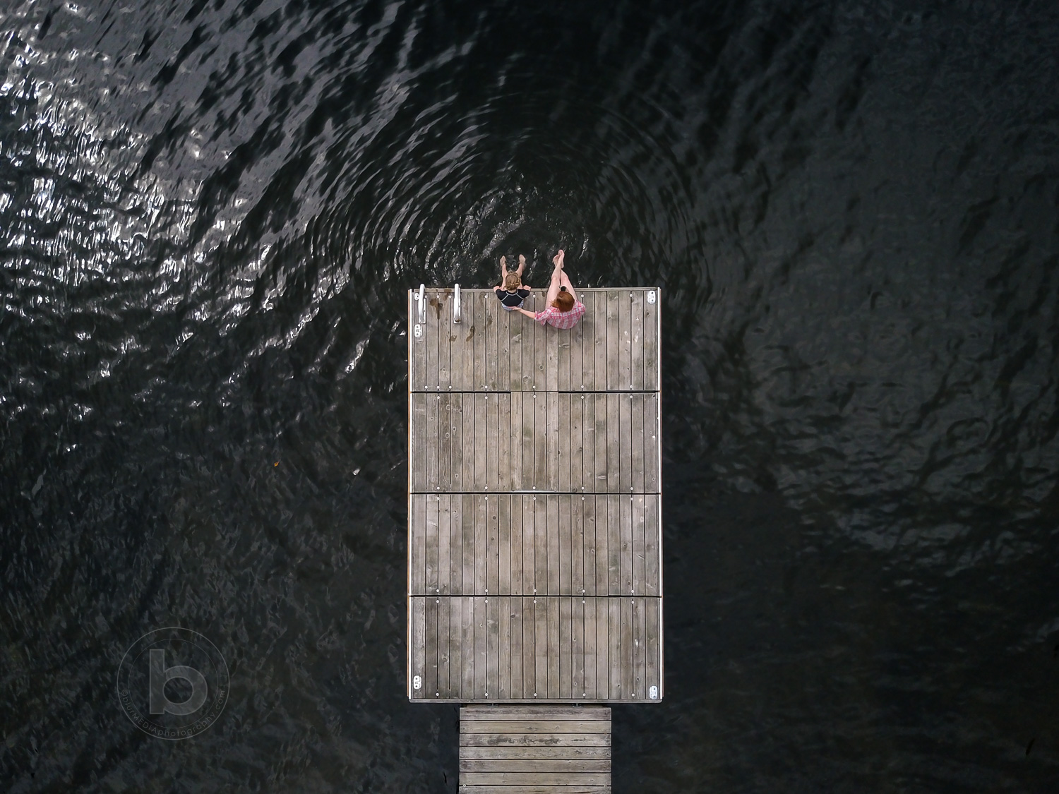 Aerial photo of a woman (40) and girl (11) sitting on a wooden dock at a lake in the Kawartha cottage region near Haliburton, Ontario, Canada