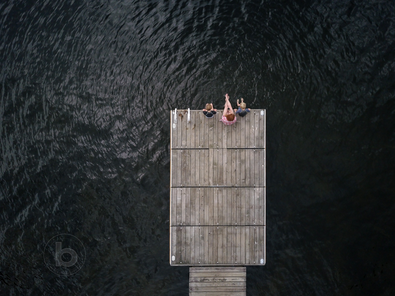 Aerial photo of a woman (40) girl (11) and boy (9) sitting on a wooden dock at a lake in the Kawartha cottage region near Haliburton, Ontario, Canada