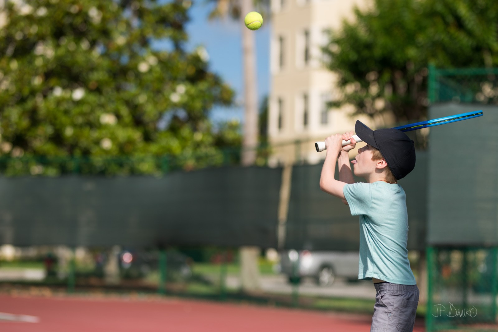 Boy makes a strong effort to return ball playing tennis for fun with mom on summer Florida vacation