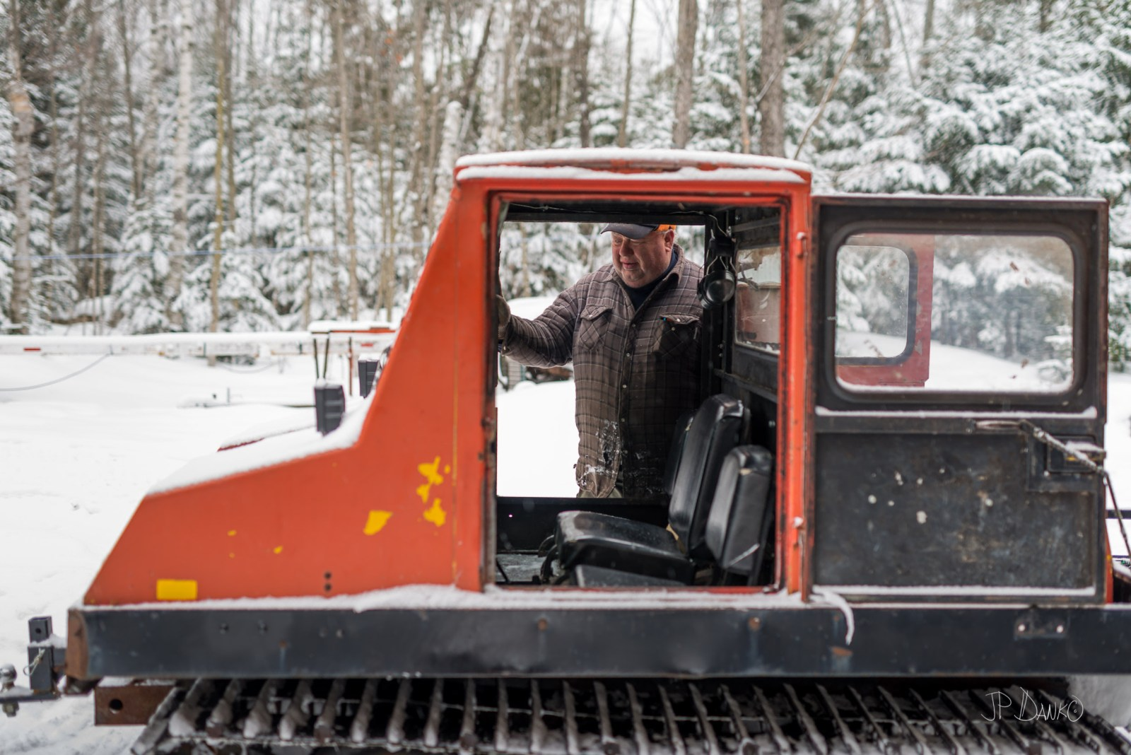 Rustic northern Ontario man steps into cab of snow grooming machine