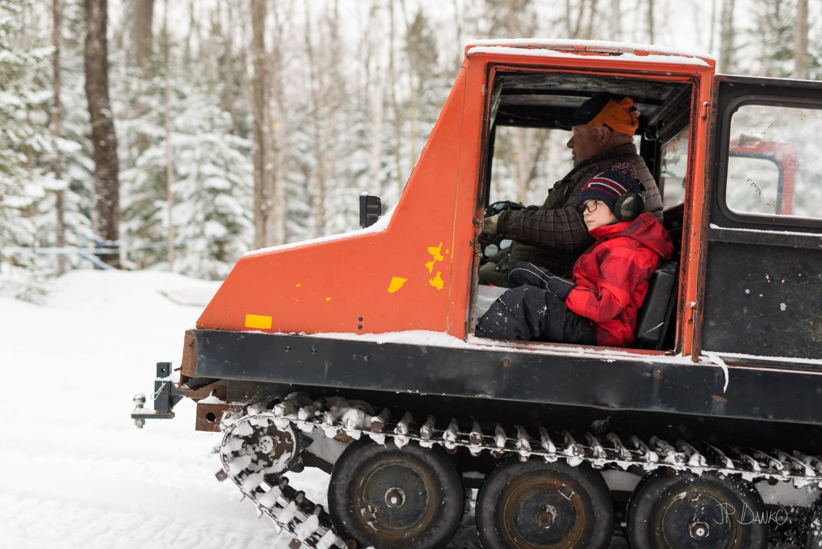 Boy calm in serene winter scene getting ride in old man's snow grooming machine