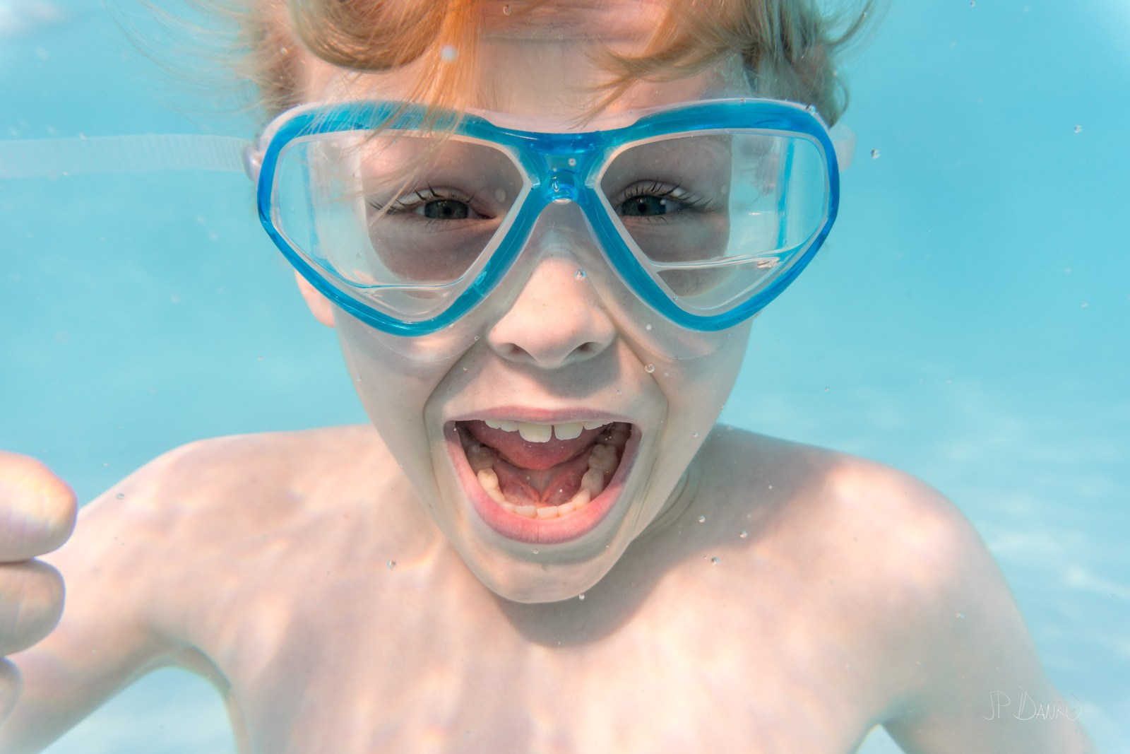 Underwater view of redhaired boy diving in cool blue holiday swimming pool