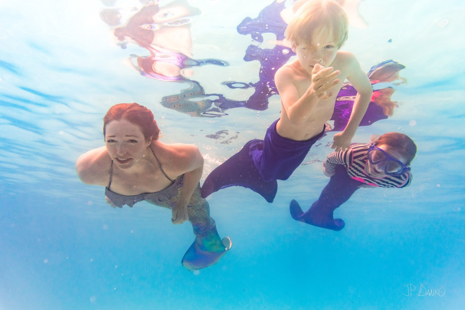 Underwater view of mom sond and saughter on holiday swimming in pool with colorful mermaid tails