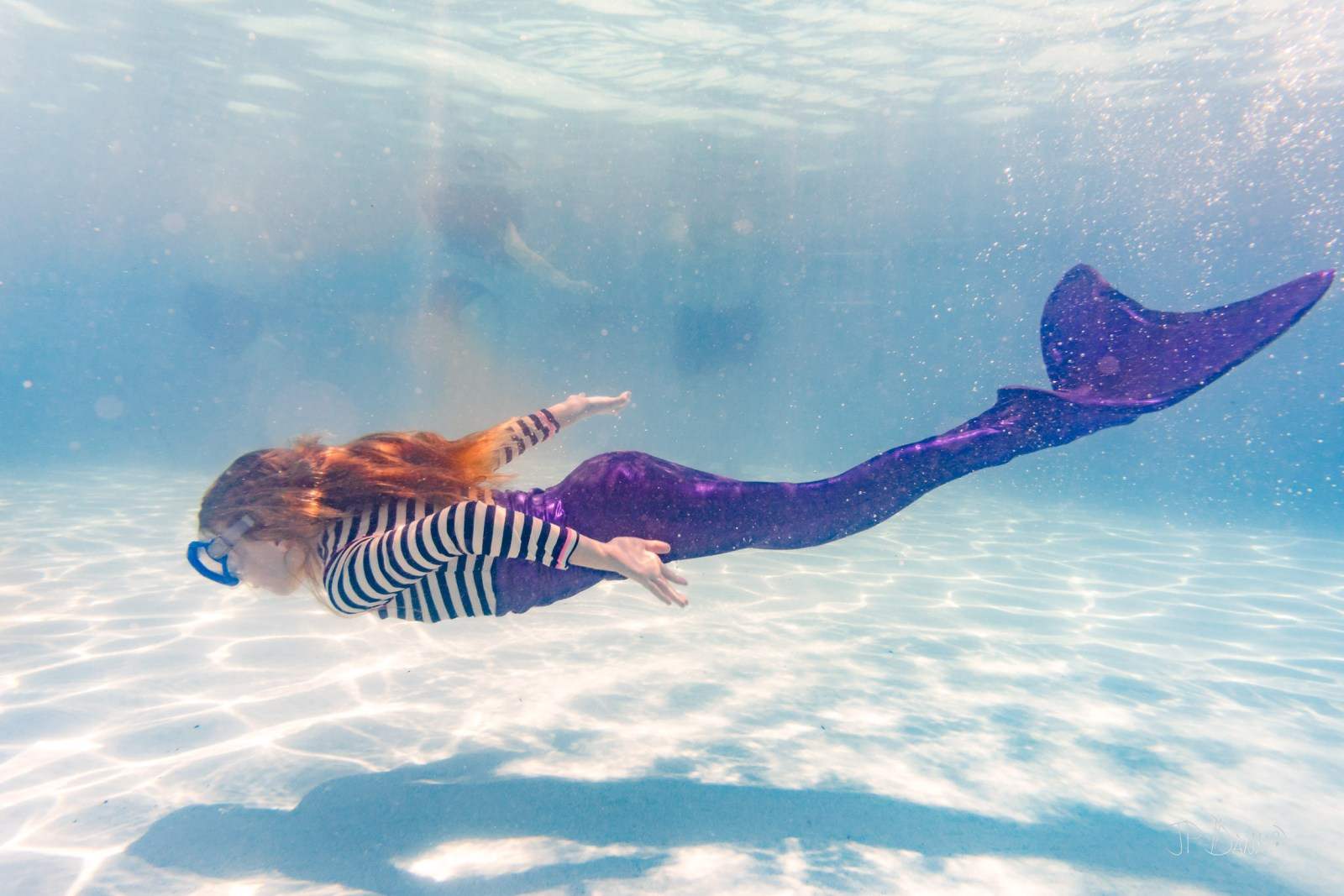 Underwater view of girl on holiday swimming in pool with colorful mermaid tail