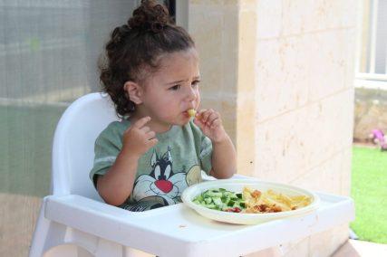 Bebé comiendo sola en la trona