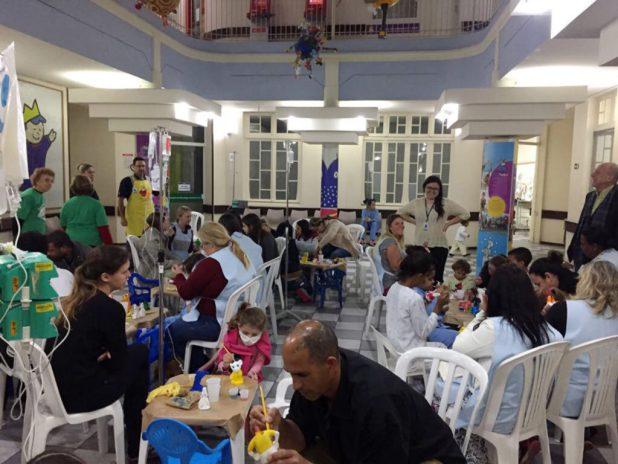 Visão geral do salão utilizado para a divertida e alegre atividade do Projeto Tikun Olam, com os pais auxiliando os filhos na pintura em gesso