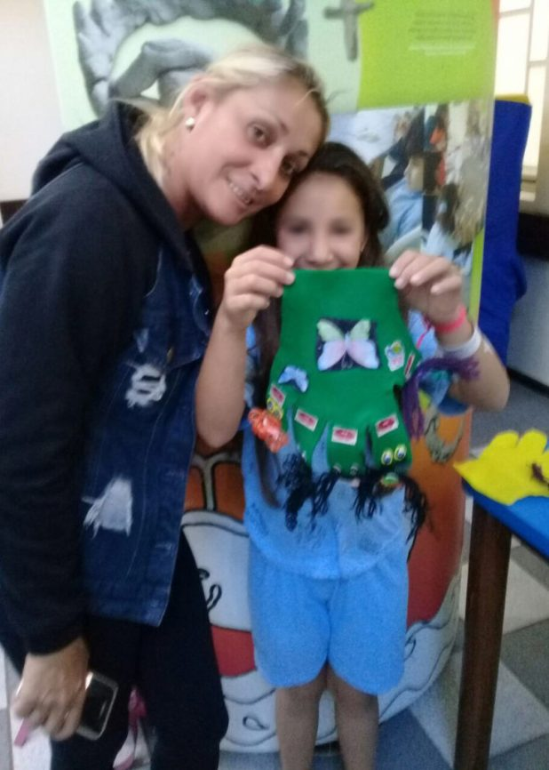 A luva de enfeite após ser decorada é exibida pela artesã infantil