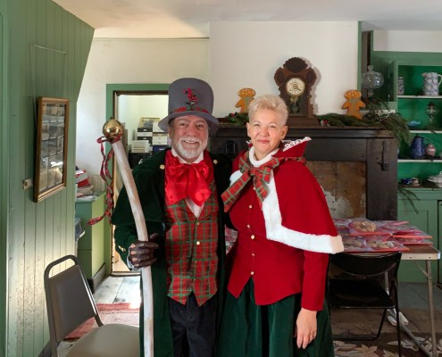 A couple in Victorian Christmas costumes