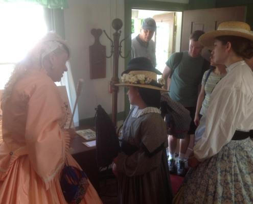Women in hoop skirted costumes looking at an exhibition