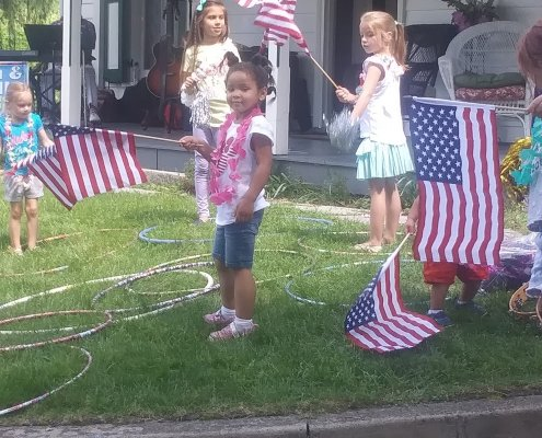 Children waiving American flags outside of the museum