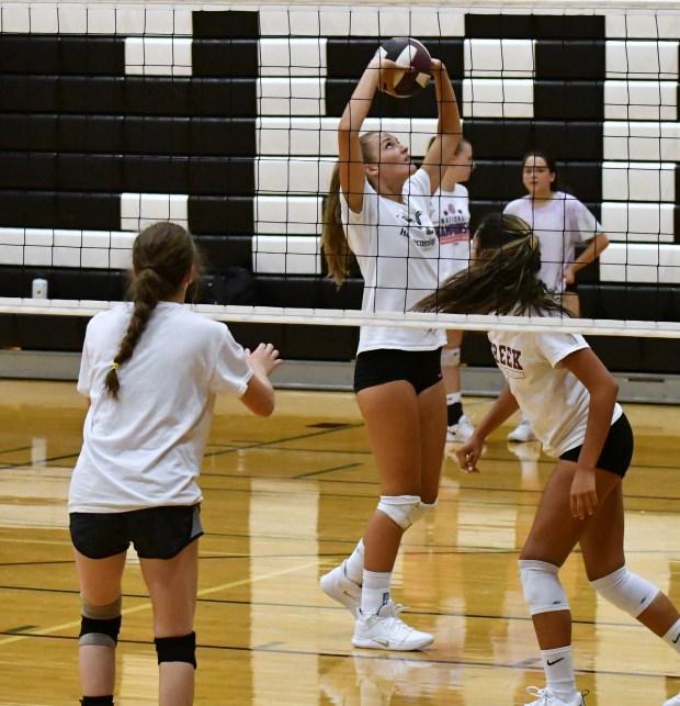 Caitlin Volkmann, center, sets the ball ...