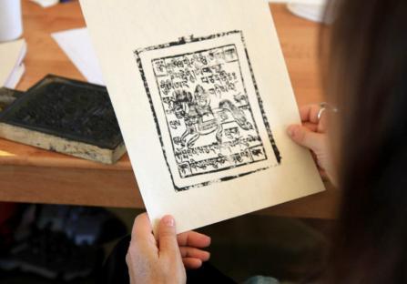 Parent studies a woodcut
