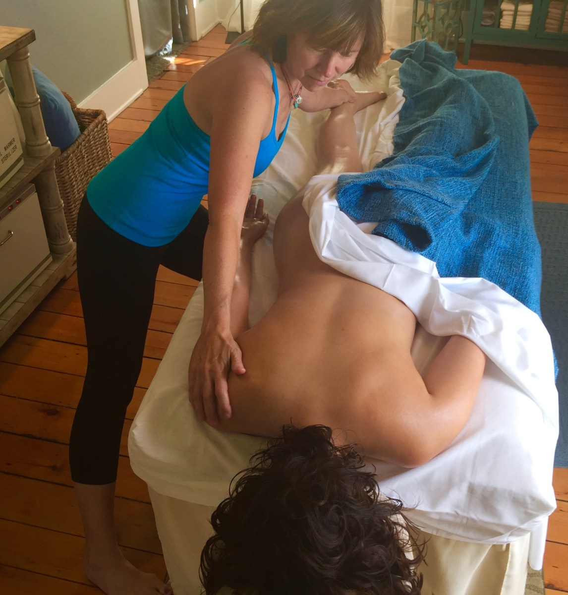Massage therapist with hand on shoulder and foot of client