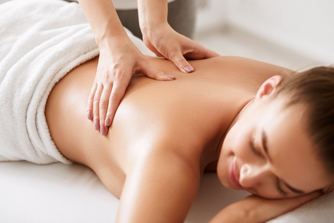 young-girl-receiving-back-massage-with-closed-eyes