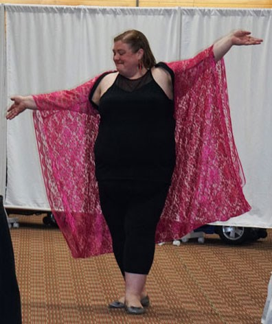 A fat white woman with shoulder-length brown hair throws her arms wide in joy and confidence as she walks in a fashion show in front of a white sheet. She's wearing a black sleeveless top and pants with a bright pink lace kimono-style jacket.