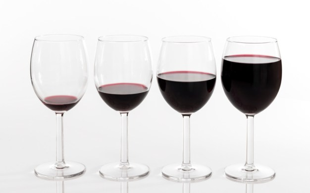 Four glasses filled with different quantities of red wine.