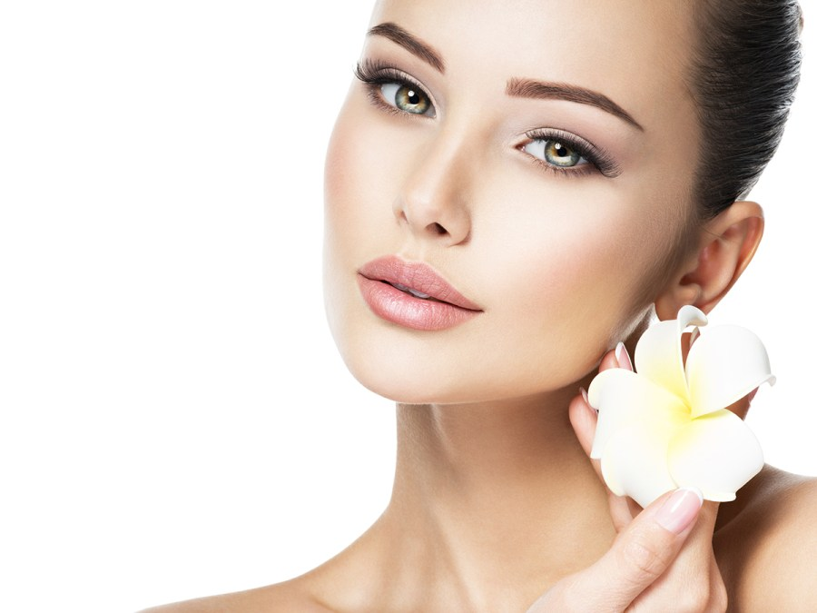 Beautiful face of young woman with flower. Clean healthy skin.