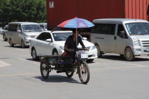 Mopedfahrer mit Sonnenschirm